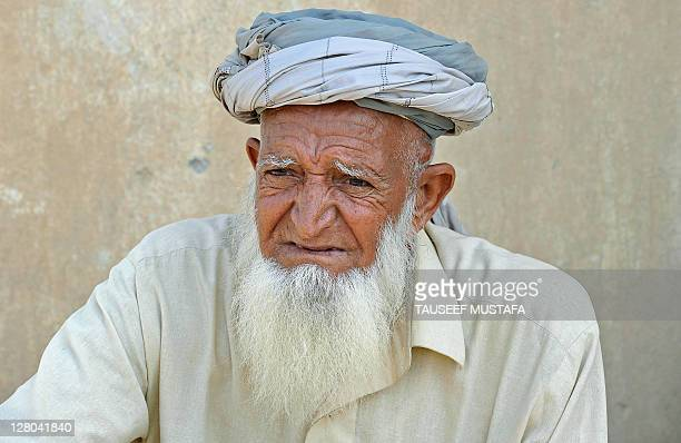 An old Afghan man looks at US army soldiers from HHB 37 Field Artillery Regiment 3rd Bct 25th ID patrol during their mission in Turkham Nangarhar...