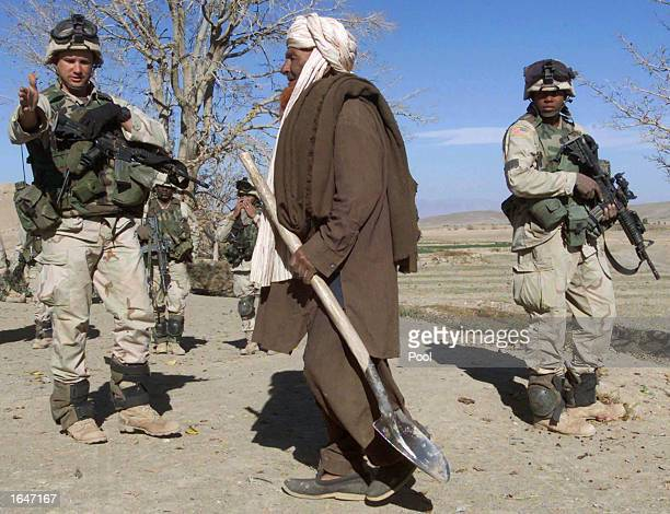 An old Afghan man walks by US soldiers of the 82nd Airborne Division during an operation of searching compounds November 13 2002 in the town of Ahad...