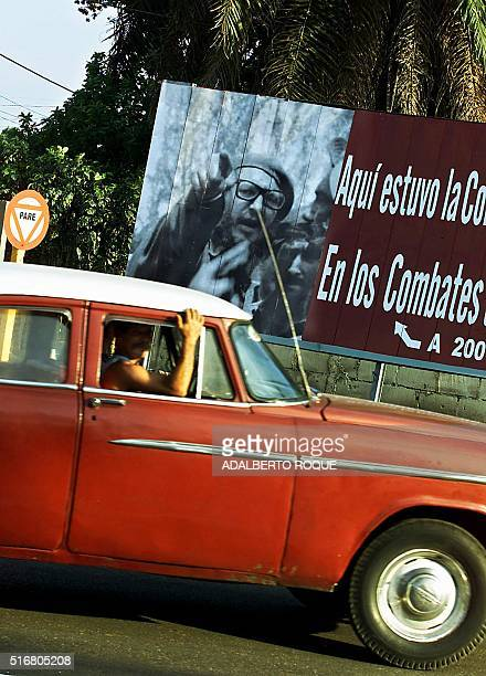 An old American car passes 19 April 2001 in front of a poster referring to the 40th anniversary of the Cuban armed forces victory in Playa Giron Bay...