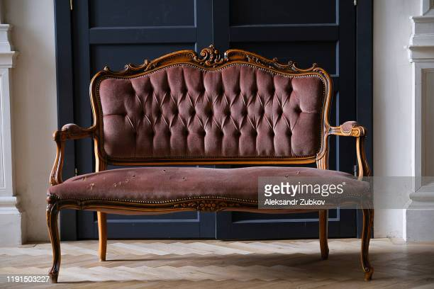 an old antique sofa, with holes in the fabric. - antique stock pictures, royalty-free photos & images