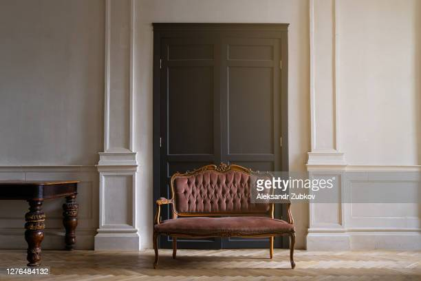 an old antique sofa with holes in the fabric. the interior of the room is in a retro style. - chair stock pictures, royalty-free photos & images