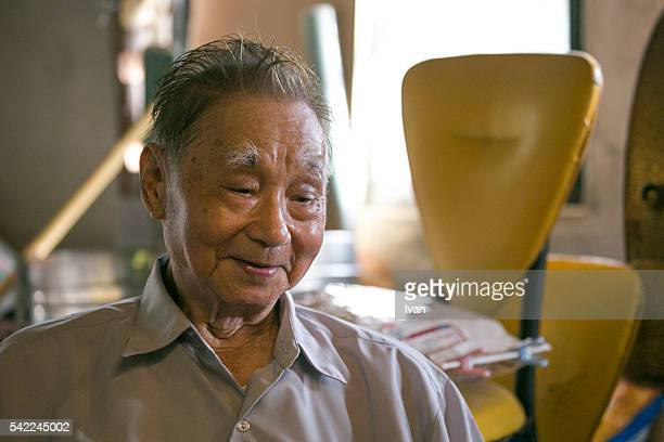 An Old Asian Man, Grandpa, Looking Down and With Kindly and Anxious Eyes