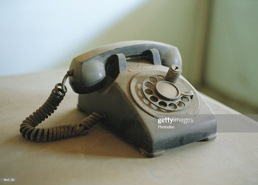 an old blue rotary phone rests on a white table in a white room : Foto de stock