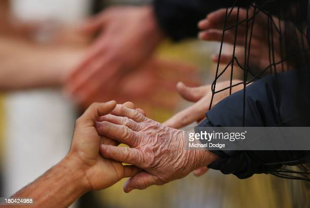 An old Blues fan reaches through the net to slap a players hand during a Carlton Blues AFL training session at Visy Park on September 13 2013 in...