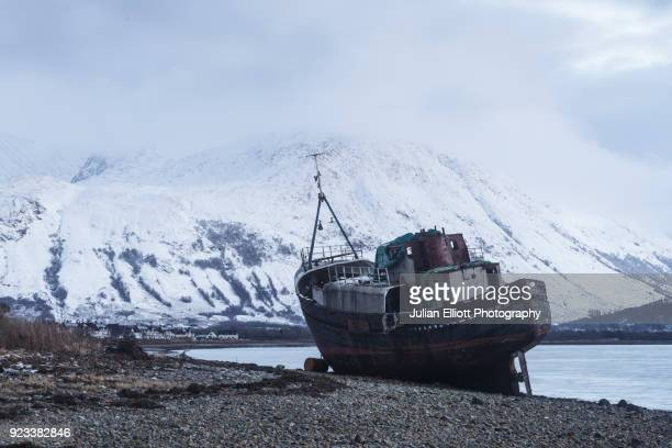an old boat on loch linnhe with ben nevis in the background. - abandoned stock pictures, royalty-free photos & images