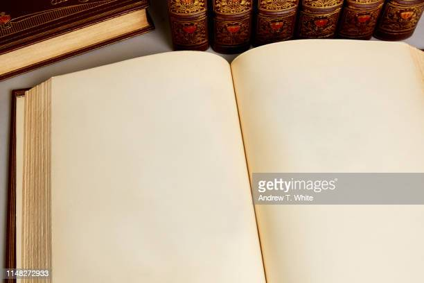 an old book with blank pages sits with collection of antique rare and old leather bound books from the 19th century - old book stock photos and pictures