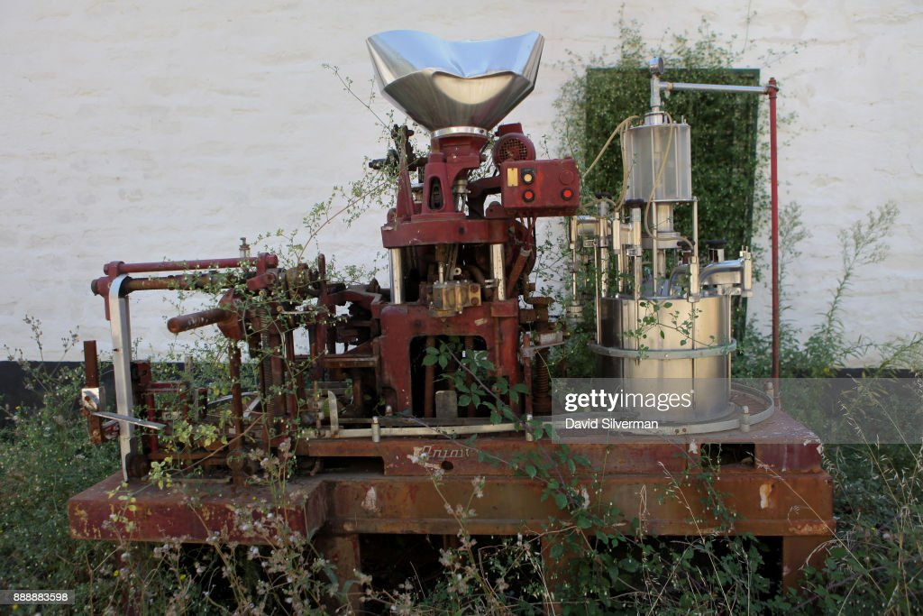 An old, broken-down wine-bottling machine gathers rust and is
