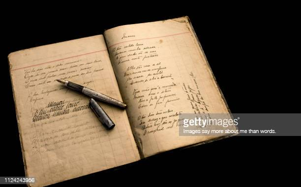 an old calygraphy notebook opened showing the progression. an old silver pen rests upon it. still life - the past stock pictures, royalty-free photos & images