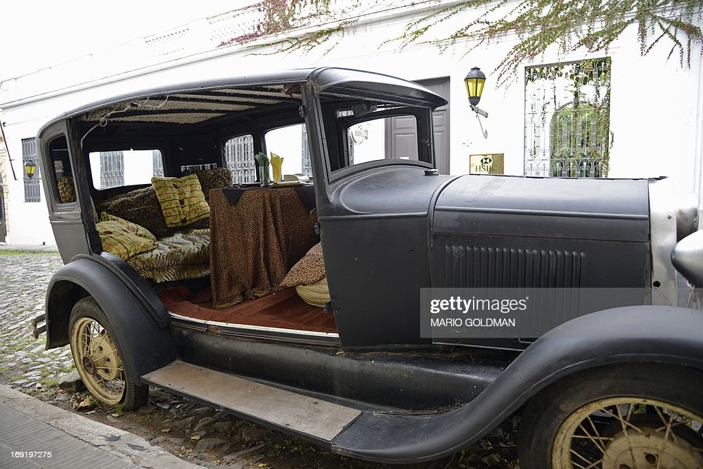 An old car decorates the historic quarter section of Colonia del ...