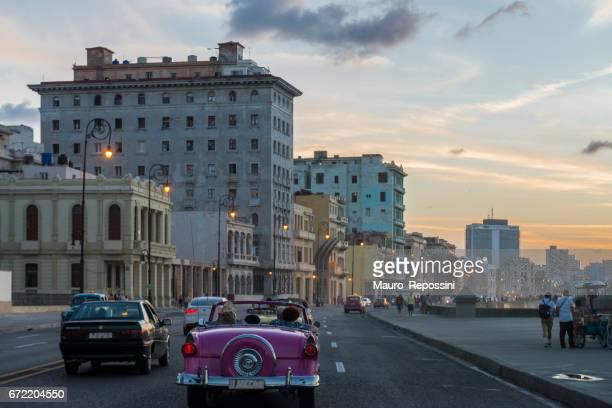 An old car driving along the malecon at Havana, Cuba.