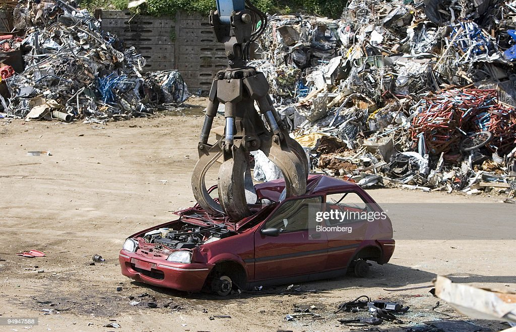 An old car for crushing is picked up by a claw at a scrap me ...