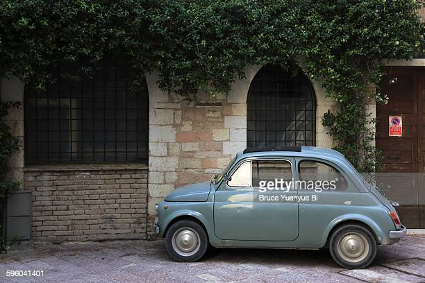 an old car parking on street of assisi - compact car stock photos and pictures