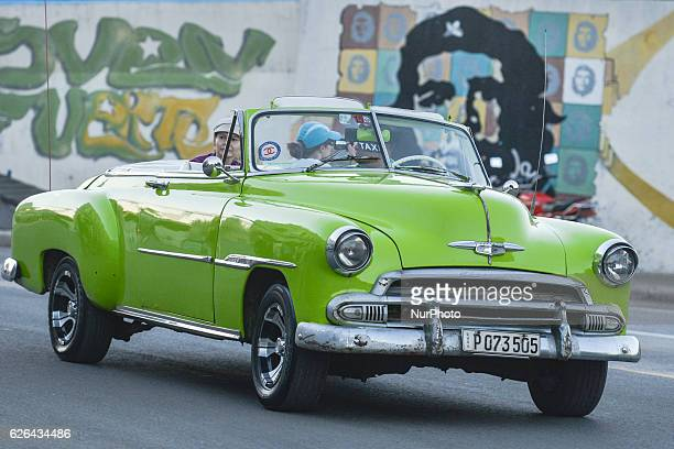 An old car passes by Che graffiti a scene from the street in Havana city center on November 28 the third day after Fidel Castro Cuba's historic...