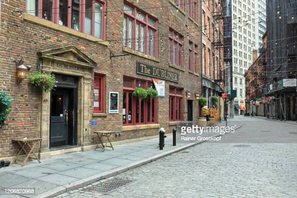 an old cobblestone street with restaurants and pubs in new york - rainer grosskopf stock pictures, royalty-free photos & images