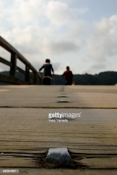 An old couple crossing Kintaikyo Bridge
