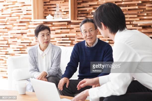 Ein altes Ehepaar, hören Geschichten von einem Mann in einem Anzug.