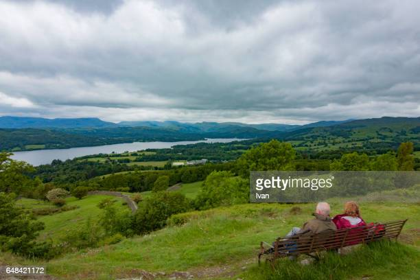An Old Couple Siting on a Wood Beach Chair,  Surrounding by Mountain, Lake and Beautiful Nature Scenes, England, UK