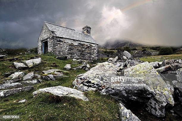 An old derelict farmhouse on a craggy hillside with heavy cloud and a rainbow overhead taken on November 17 2008