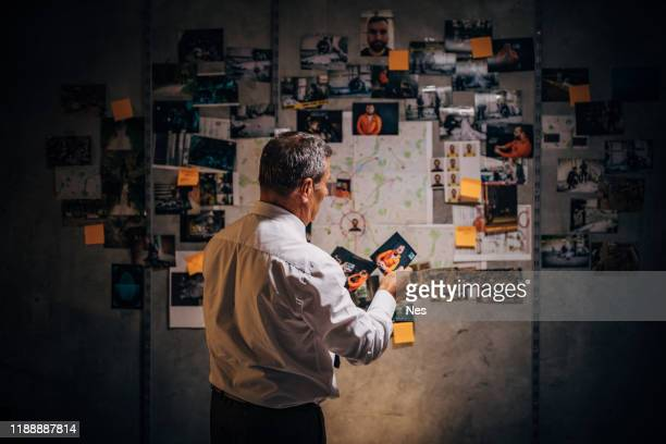 an old detective is looking at photos of suspects in his office - detective stock pictures, royalty-free photos & images