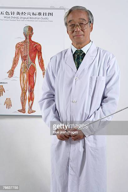 An old doctor is standing with a pointer.
