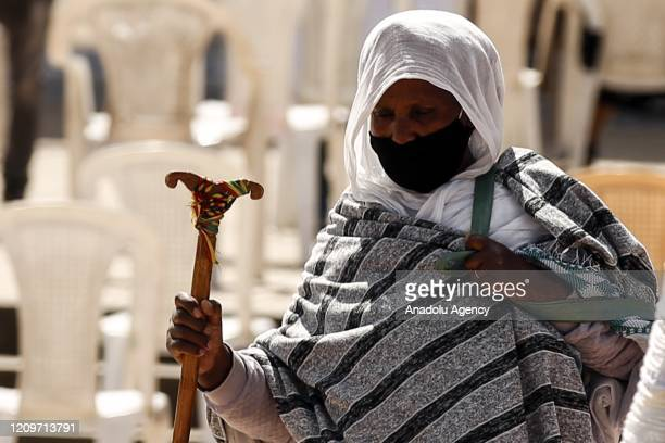 An old Ethiopian Orthodox Christian woman wears a face mask as a preventive measure against the coronavirus pandemic while making her way to attend...