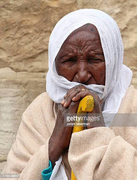 An old Ethiopian woman, sitting, leaning her hands on a walking stick, at the Legs Washing Ceremony, at the Church of the Holy Sepulchre. She is...