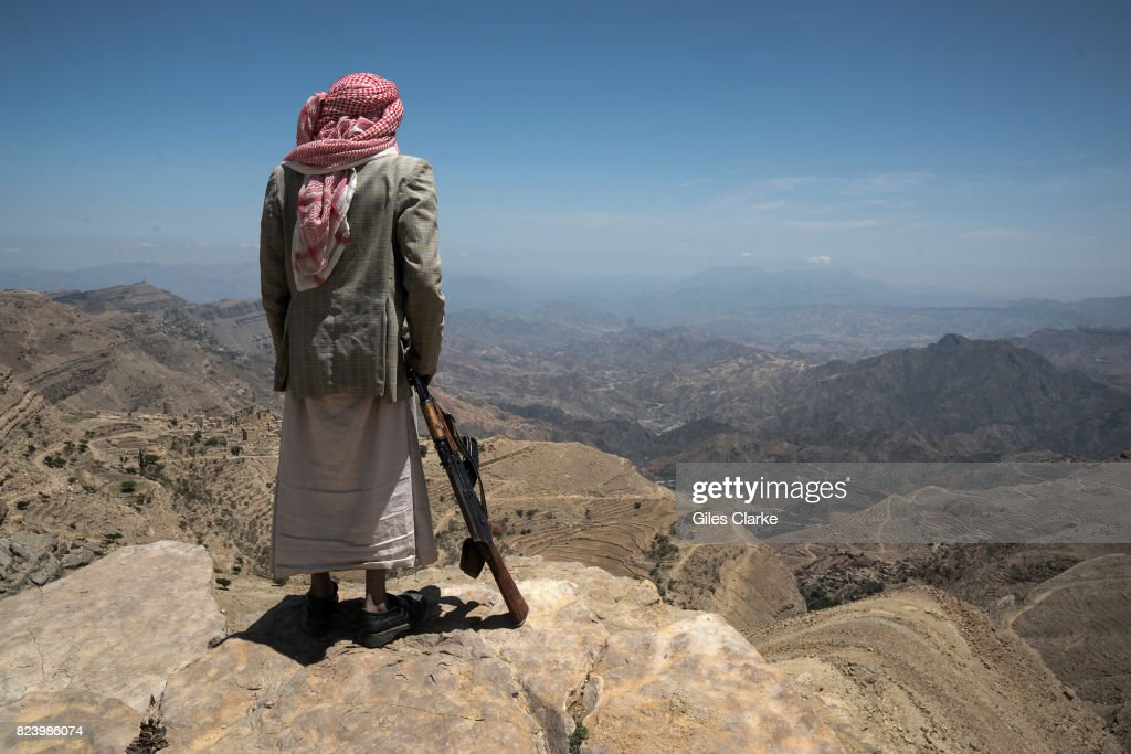 An old farmer with his gun stands in the mountains of Yemen.