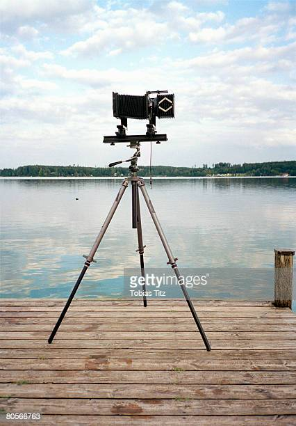 An old fashioned camera on a tripod in front of a lake