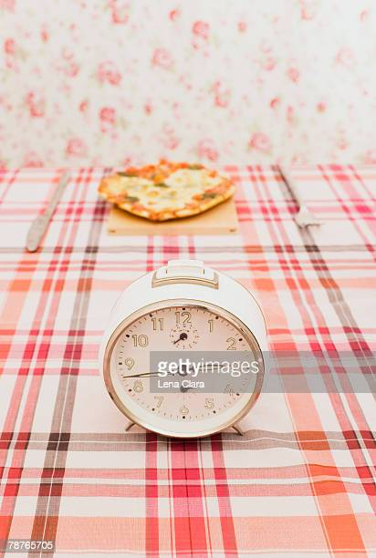 An old fashioned clock on a table with a pizza