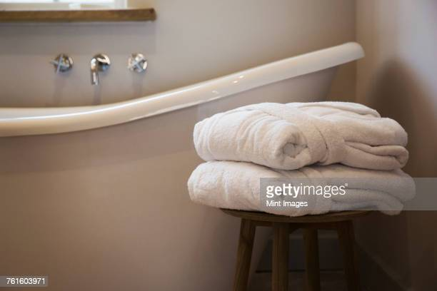 an old fashioned slipper shape bathtub, bath with raised end and wall mounted taps in a bathroom. two folded guest bathrobes on a stool.  - towel stock pictures, royalty-free photos & images