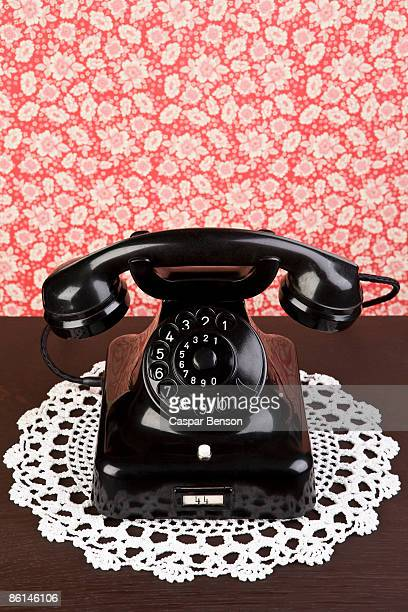 an old fashioned telephone on a dresser - doily stock photos and pictures