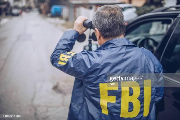 古いfbiエージェントは、観察のために双眼鏡を使用します - fbi ストックフォトと画像