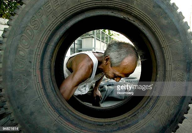 An old Filipino rubber expert patches damaged tires at his roadside vulcanization shop in central Manila Philippines March 22 2005