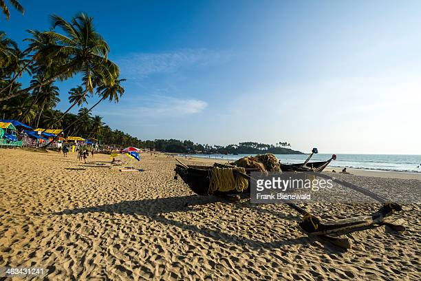 An old fishing boat at Palolem Beach with blue sky palm trees white sand and blue sea