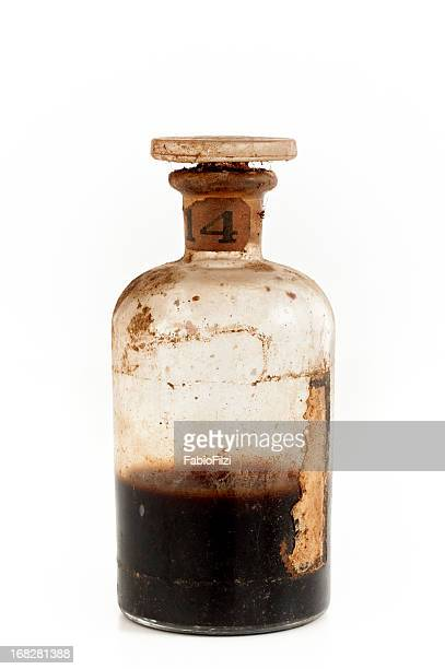 an old glass bottle half filled with brown poison - potion stock photos and pictures