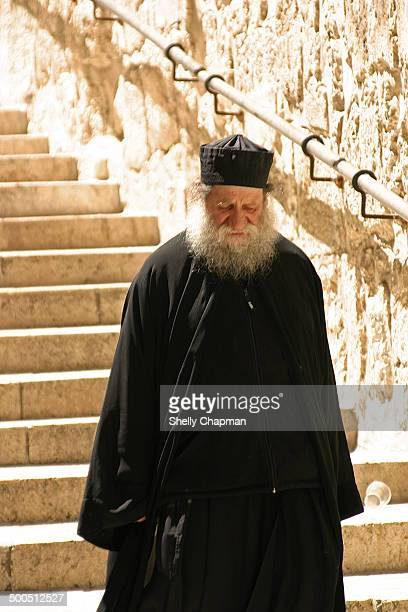 An old Greek Orthodox Priest, deep in thought, walking towards the Church of the Holy Sepulchre, in the ancient city of Jerusalem, Israel.