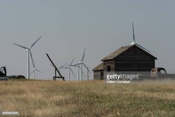 An old homestead in front of wind turbines on private working ranch land on August 1 2017 near Kevin Montana The Rim Rock Wind Farm is operated by...