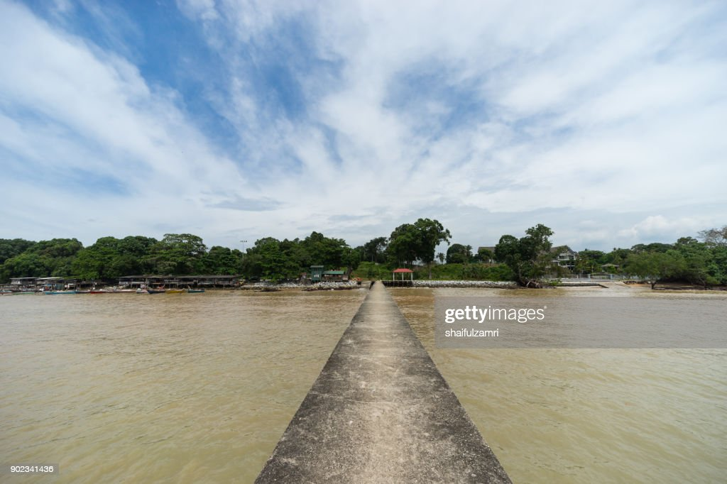 PORT DICKSON, MALAYSIA - 24TH DEC 2017; An old jetty on the still water at Port Dickson, Malaysia stretches towards to horizon : Stock Photo