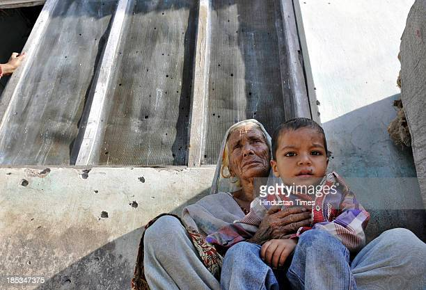 An old lady along with her grandson sitting near bullet holes on the wall of a home in Najwal village on October 19 2013 in Pargwal sector of Akhnoor...