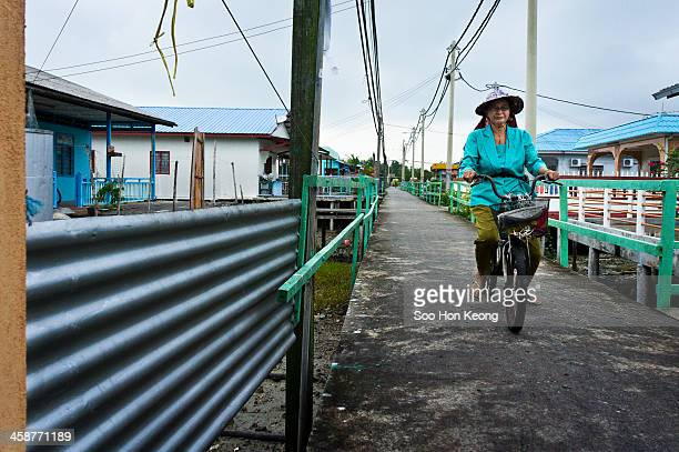 An old lady cycling in a lane at Pulau Ketam which literally translated as 'Crab Island'. It is small island located off the coast of Port Klang,...