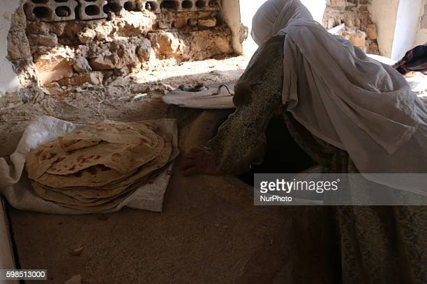 An old lady making oven for cooking bread from the dust of the works on wood rather than gas in the eastern Ghouta Sakba in East Ghouta of Damascus...