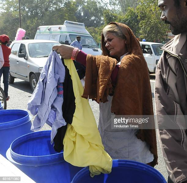 An old lady pick up clothes from a collection box installed during an inauguration of weeklong programme of Happiness Department 'Anandam' on the...