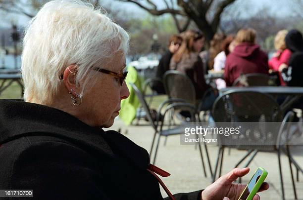 CONTENT] An old lady using her smartphone while youth can be seen hanging out behind her An interesting contrast where an elderly person is using new...