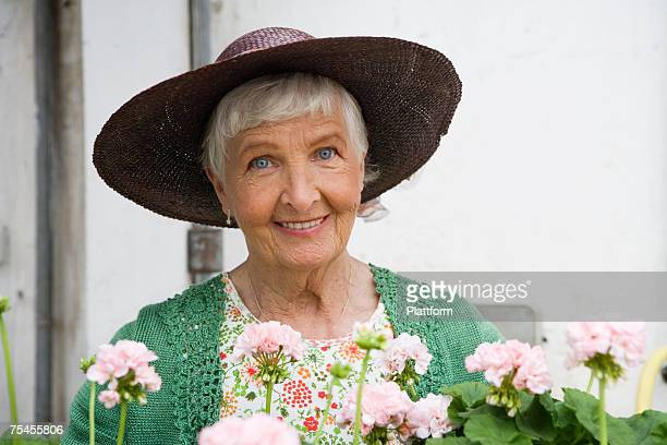 An old lady with flowers in a green house, Sweden.