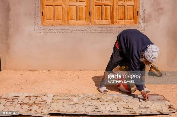 An Old Lao Lady Bends Down To Dry Rice Cakes In The Sun On The Ground Outside. In The Town Muang Khua. Laos.