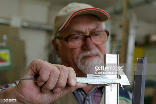 An old locksmith taking the measurement of a piece of metal
