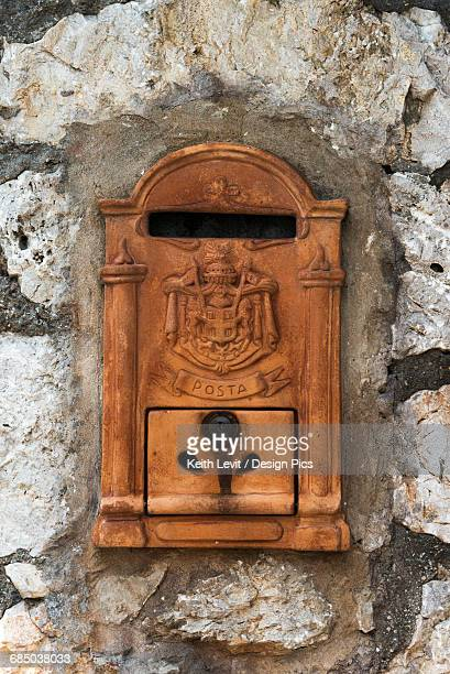 An old mailbox in a weathered stone wall