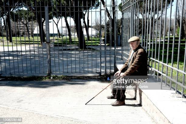 An old man alone in front of a closed park for measures against coronavirus infection on March 25 2020 in Rome Italy The Italian government continues...