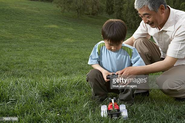an old man and a boy are playing with a remote control car. - remote control car games stock photos and pictures