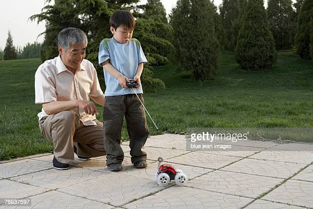 An old man and a boy are playing with a remote control car.